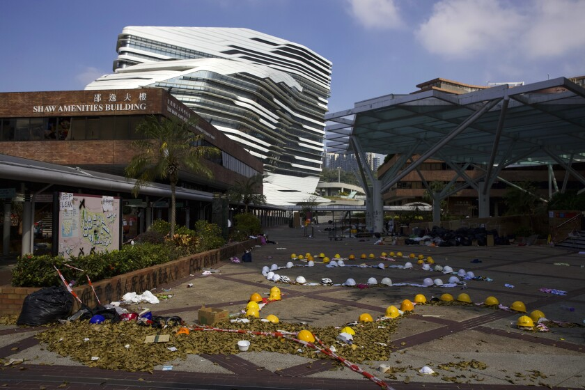 Hard hats and pieces of cloth linked to form the words SOS, placed by protesters, are seen on the Hong Kong Polytechnic University campus in Hong Kong, Wednesday, Nov. 27, 2019. A major tunnel in Hong Kong reopened on Wednesday as a weeklong police siege of a nearby university appeared to be winding down, closing one of the more violent chapters in the city's anti-government protests. (AP Photo/Ng Han Guan)