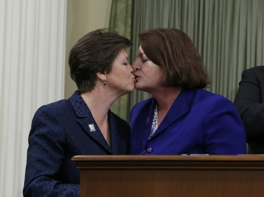FILE - In this Monday, May 12, 2014 file photo, Democrat Toni Atkins, of San Diego, right, kisses her spouse, Jennifer LeSar, after she was sworn in as the 69th Assembly Speaker at the Capitol in Sacramento, Calif.    Atkins told an audience of women Tuesday, June 17, 2014, there was nothing courag