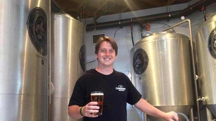 Michael Dykstra, General manager of Coronado Brewing Pub, holding a Bock Ness in the brewery. (Liz Bowen)
