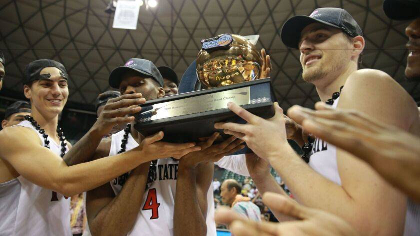 The San Diego State Aztecs hold the championship trophy at Stan Sheriff Center after winning the Diamond Head Classic.