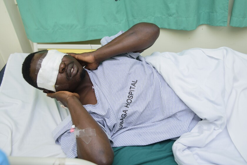"""Mityana Municipality politician, Zaake Francis, close ally to opposition leader Bobi Wine gestures, in Rubaga hospital, Kampala, Uganda, Sunday, Jan. 17, 2021, after he was alledgedly beaten by security personnel at the gates of Bobi Wine's house on Saturday. A day after Uganda's longtime leader was declared the winner of the country's presidential election, the opposition party dismissed the results as """"fraud"""" and called for the release of their leader, Bobi Wine, who has been under alleged house arrest for several days. (AP Photo/Nicholas Bamulanzeki)"""