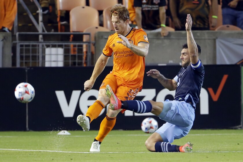 Houston Dynamo's Tim Parker (5) kicks away the ball as Vancouver Whitecaps' Lucas Cavallini (9) slides in to block during the second half of an MLS soccer match Saturday, May 22, 2021, in Houston. (AP Photo/Michael Wyke)