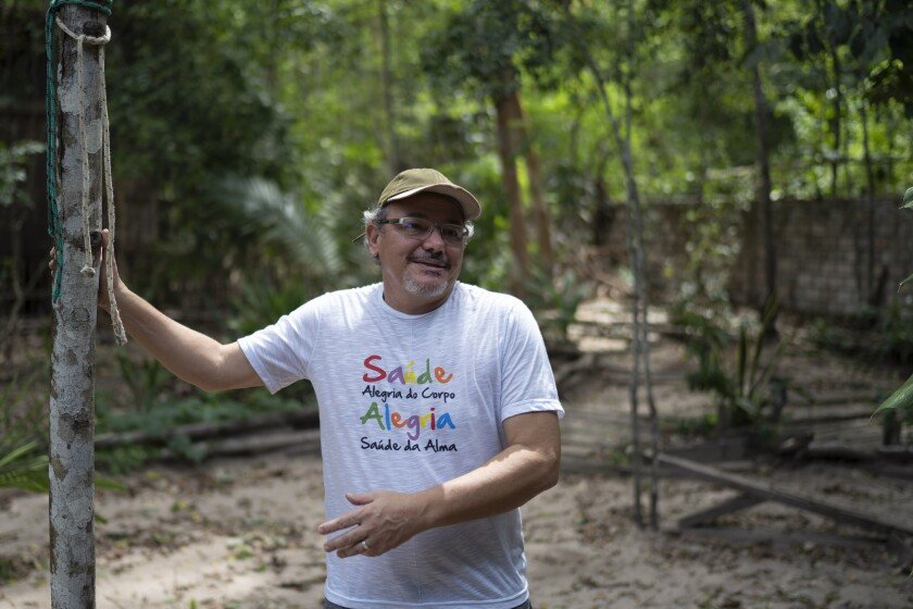 """In this Dec. 1, 2019 photo, Caetano Scannavino, coordinator of NGO """"Saude e Alegria,"""" or Health and Happiness, gives an interview outside his home in Alter do Chao, Para state, Brazil. The sleepy Amazon town has become the flashpoint for the growing hostility between Brazil's far-right President Jair Bolsonaro and environmental groups following the arrest of firefighters he says set rainforest fires. (AP Photo/Leo Correa)"""
