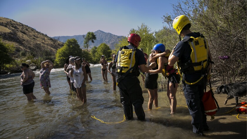 Shannon Gilbert, second from right, gets a hug after being rescued. She was tubing without a life ve