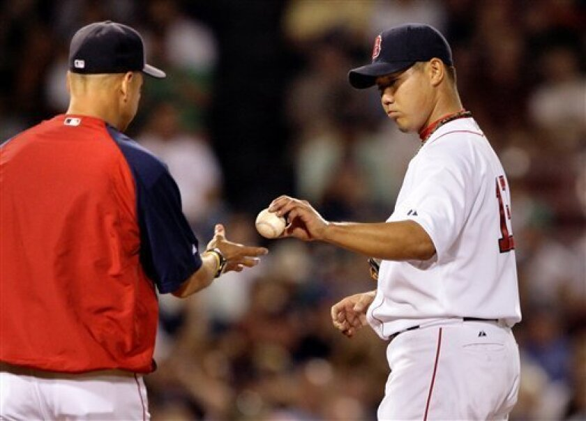 Boston Red Sox pitcher Daisuke Matsuzaka, right, gives the ball to manager Terry Francona as he is pulled after giving up five runs in the seventh inning against the Los Angeles Angels during their MLB baseball game at Fenway Park in Boston, Monday, July 28, 2008. (AP Photo/Charles Krupa)