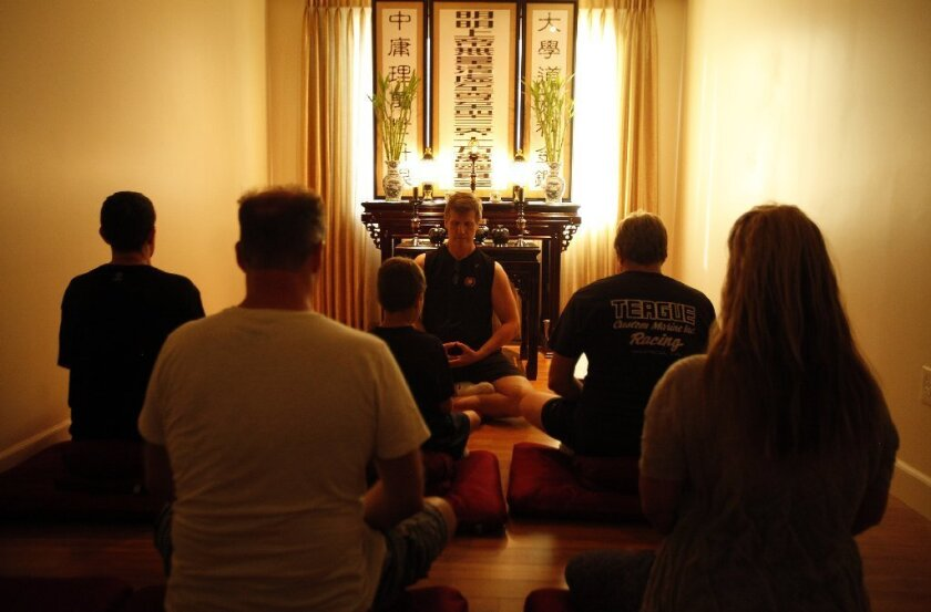 Students meditate during a class at the Ekata fitness center in Valencia.