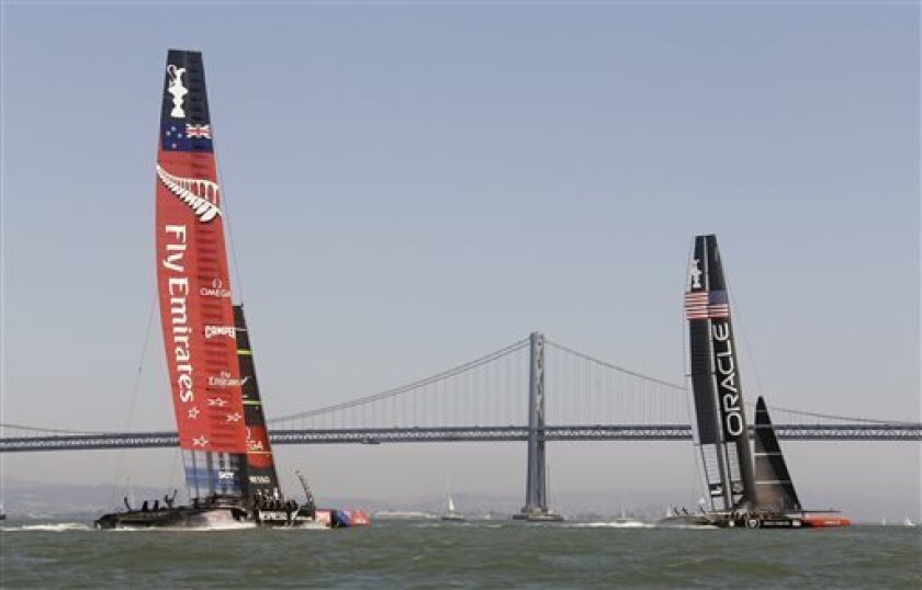 Oracle Team USA, right, goes past the finish line ahead of Emirates Team New Zealand, left, to win the fourth race of the America's Cup sailing event Sunday, Sept. 8, 2013, in San Francisco. Emirates Team New Zealand won the third race and Oracle Team USA won the fourth race Sunday. In the background is the San Francisco-Oakland Bay Bridge. (AP Photo/Eric Risberg)
