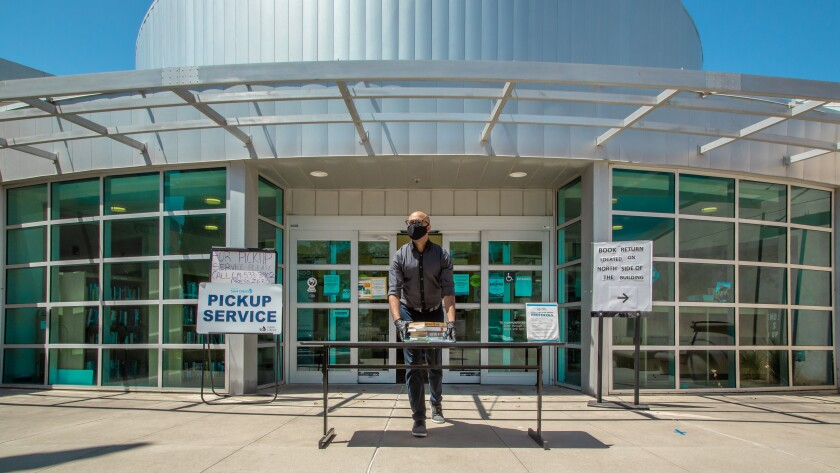 A worker places books on a table outside the College-Rolando library branch for pickup during COVID closure