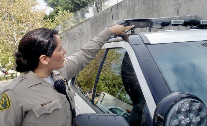Deputy Cristina Cordoba, with the Crescenta Valley Sheriff's Station, points to a camera device mounted on the roof that is able to capture and store vehicle license plate numbers to help with current and future investigations.