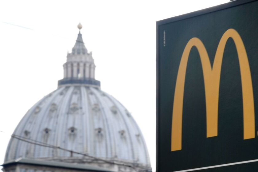 A sign showing the direction of a McDonald's restaurant is seen with the cupola of St Peter's Basilica in the background in Rome. The fast-food chain opened a restaurant in a Vatican-owned building despite protest of a Committee for the Protection of Borgo, the historic district around the Vatican where many cardinals live.
