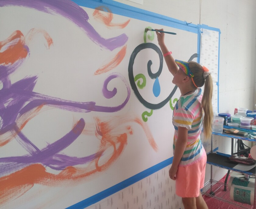 """Brooke Sutherland adds a touch of color to a collaborative painting at the """"Abstract Mural"""" station."""