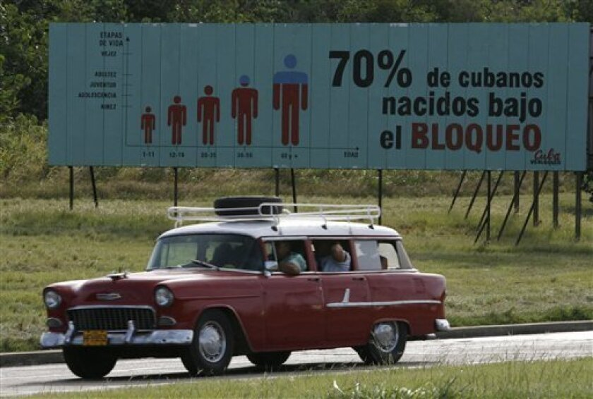 """In this Tuesday, Nov. 7, 2006 file photo, a car passes next to a billboard that reads """"70 percent of Cuban people have been born under the Embargo"""" in a highway in Havana, Cuba. A reader-submitted question about the U.S. sanctions against Cuba is being answered as part of an Associated Press Q&A column called """"Ask AP"""". (AP Photo/ Javier Galeano, FILE)"""