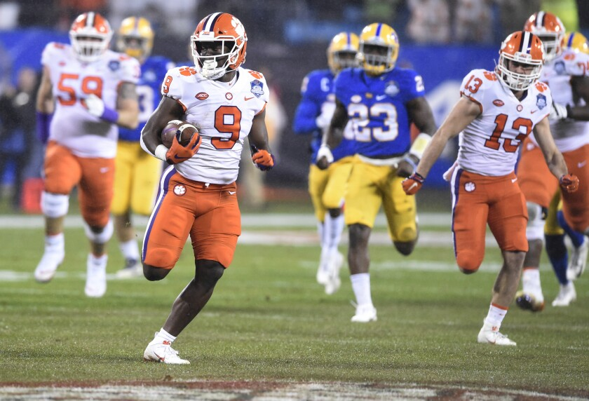 FILE - In this Dec. 1, 2018, file photo, Clemson's Travis Etienne (9) runs for a touchdown against Pittsburgh during the first half of the Atlantic Coast Conference championship NCAA college football game in Charlotte, N.C. The College Football Playoff is considering expanding from four to 12 teams to determine its champion, reserving six spots for the highest-ranked conference champions along with at-large selections. Still at least a couple of years away, CFP expansion would get a broader pool of teams involved beyond some of the usual suspects like Alabama, Clemson, Ohio State and Oklahoma. It also raises the question of how many games is too many for college players who are still juggling school and facing more wear and tear on their bodies. (AP Photo/Mike McCarn, File)