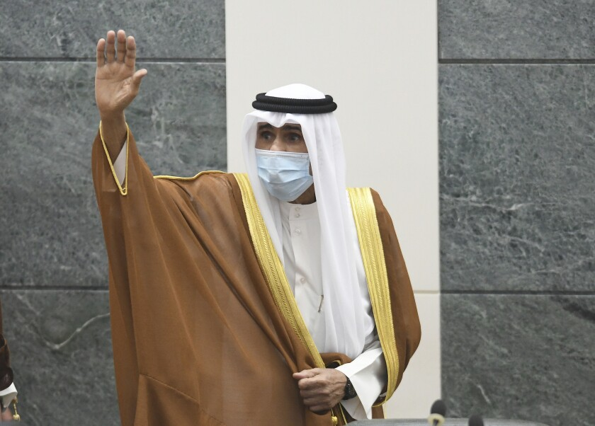 The new Emir of Kuwait Sheikh Nawaf Al Ahmad Al Sabah, waves after he performed the constitutional oath at the Kuwaiti National Assembly in Kuwait, Wednesday, Sept. 30, 2020. Kuwait's Sheikh Nawaf Al Ahmad Al Sabah was sworn in Wednesday as the ruling emir of the tiny oil-rich country, propelled to power by the death of his half-brother after a long career in the security services. (AP Photo/Jaber Abdulkhaleg)