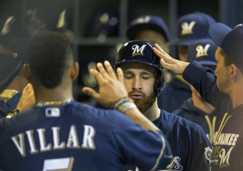Milwaukee Brewers' Jonathan Lucroy is greeted in the dugout by teammates after hitting a solo home run in the second inning off of St. Louis Cardinals' Mike Leake during a baseball game Tuesday, May 31, 2016, in Milwaukee. (AP Photo/Tom Lynn)