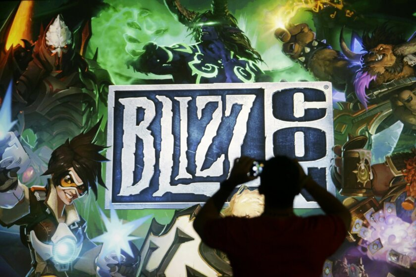 """A man takes pictures of the BlizzCon sign at the opening ceremony of the convention, Friday, Nov. 6, 2015, in Anaheim, Calif. """"World of Warcraft"""" maker Blizzard is hosting its ninth annual fan-centric convention opening Friday. (AP Photo/Jae C. Hong)"""