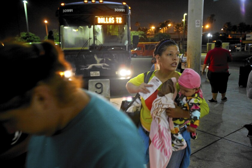 Larisa Lara of Honduras holds her 6-month-old daughter, Annie, as she boards a bus in McAllen, Texas. She spent 10 days crossing Mexico and was planning to join her father in Dallas. Many of the recent migrants are young women with children fleeing unrest back home.