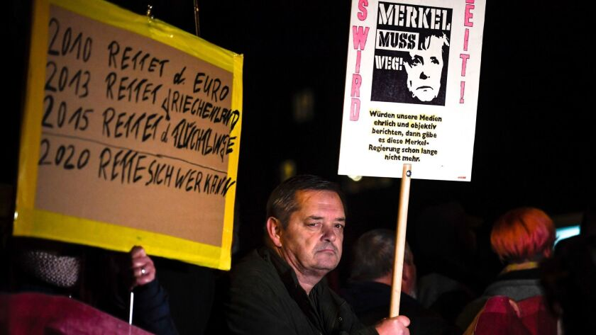 """People hold banners reading """"Merkel has to go,"""" and """"2010 Saves the Euro, 2013 Saves Greece, 2015 Saves the refugees - 2020 Save yourself who can"""" during a protest against German Chancellor Angela Merkel in Chemnitz, Germany, on Nov. 16."""