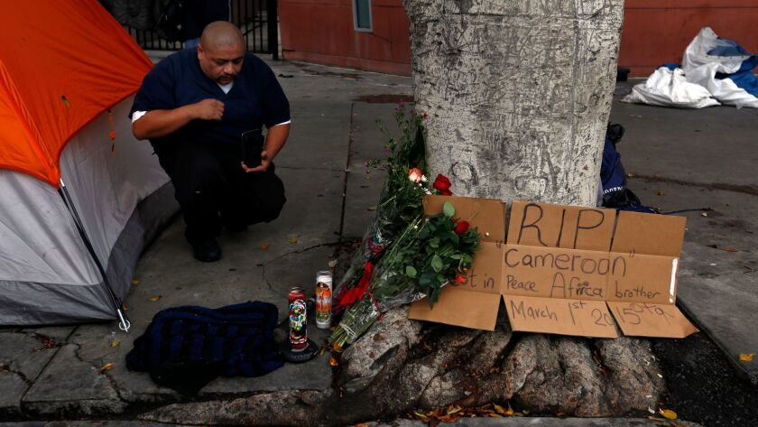 Fernando Avila kneels at a makeshift memorial for Charly Leundeu Keunang a day after the 43-year-old was shot and killed by LAPD officers on skid row in 2015.