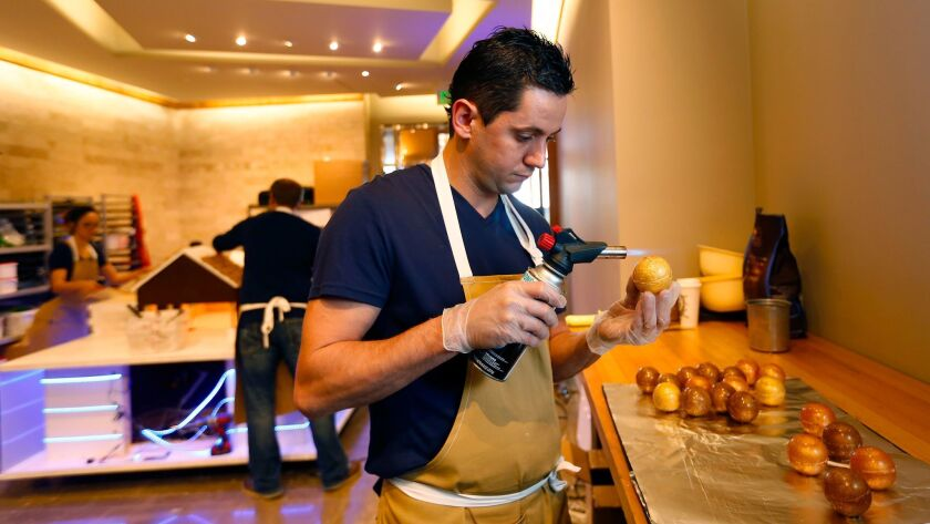Christophe Rull, executive pastry chef at the Park Hyatt Aviara in Carlsbad, uses a blow torch to smooth the surface of golden sugar ornaments that are part of an 11-foot-tall Christmas display that's almost entirely edible.
