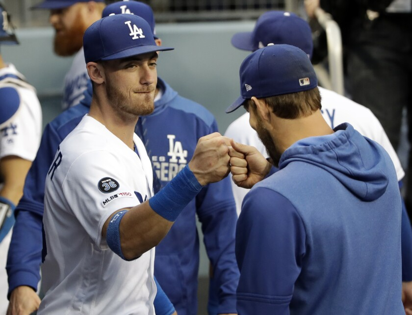 Dodgers' Cody Bellinger, left, bumps fist with Clayton Kershaw before a game June 21 at Dodger Stadium.