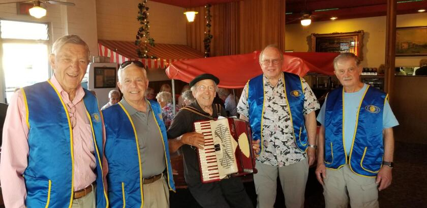 John Pernicano (center) is surrounded by Kiwanis Club members while he serenades guests with his accordion. From left: Charlie Blane, Matt Serritella, Pernicano, Steve Peterson, Jerry Hoffman