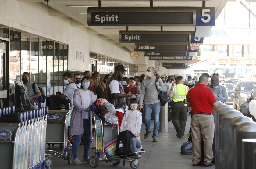 A  large crowd of passengers waits outside an airport terminal after canceled flights.