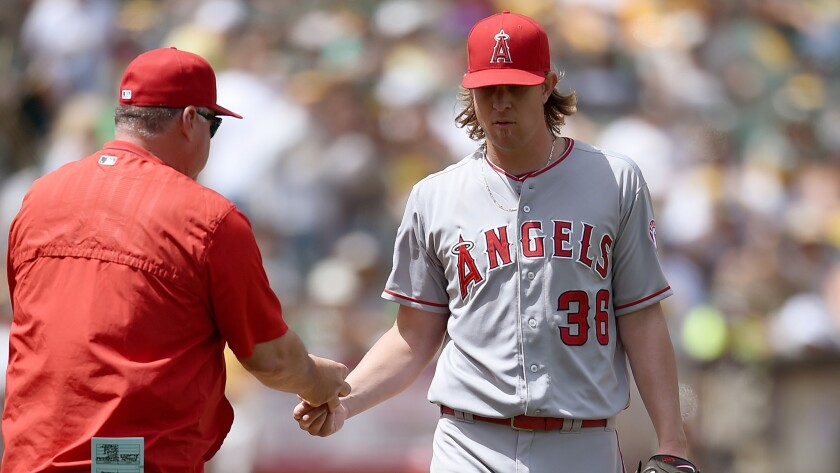 Angels Manager Mike Scioscia pulls pitcher Jered Weaver from the game during the sixth inning of a 4-1 loss to the Oakland Athletics on Saturday.