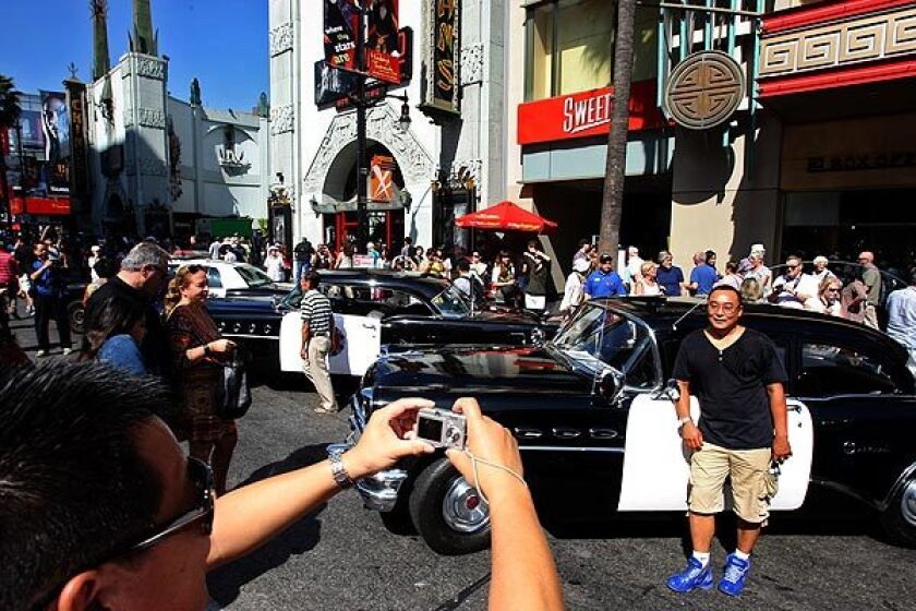 Tourists pose for pictures with vintage police cars on display in Hollywood.