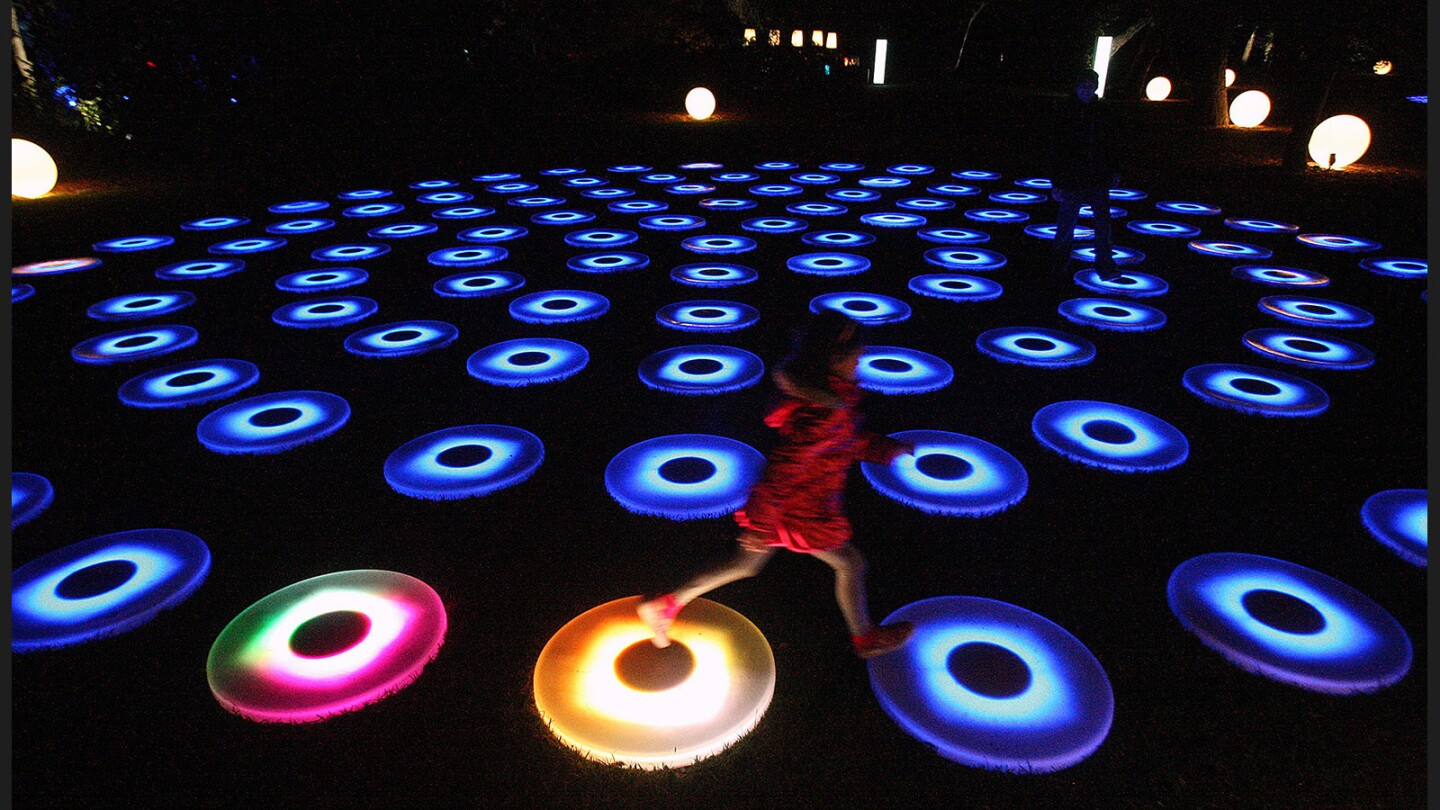 """Olivia Cremarosa, 6, of Burbank, jumps from light disk to light disk leaving a trail of color behind her on """"The Pool"""" in the """"Luminous Lawn"""" display at Descanso Garden's """"Enchanted: Forest of Light!"""" in La Cañada Flintridge on Monday, November 21, 2016."""