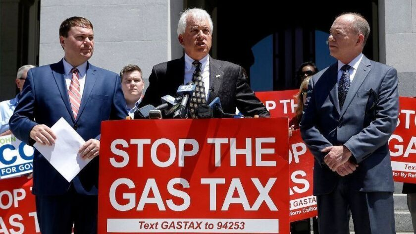 Republican gubernatorial candidate John Cox, center, blasts a recent gas tax increase during a news conference in Sacramento, Calif. Cox, chairman of a campaign to repeal the tax increase, is flanked by Carl DeMaio, left, chairman of Reform California, and Jon Coupal, right.
