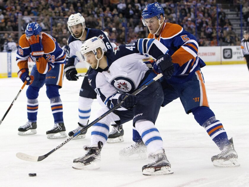 Winnipeg Jets' Joel Armia (40) is chased by Edmonton Oilers' Mark Fayne (5) during the first period of an NHL hockey game Saturday, Feb. 13, 2016, in Edmonton, Alberta. (Jason Franson/The Canadian Press via AP)