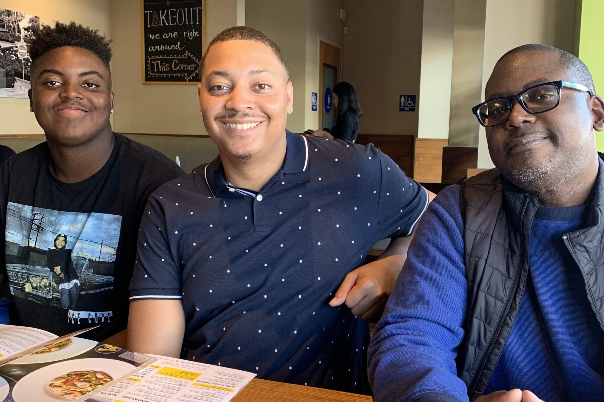 UCLA offensive lineman Jon Gaines II, left; his brother Chris Gaines, center; and his father Jon Gaines gather for a meal.