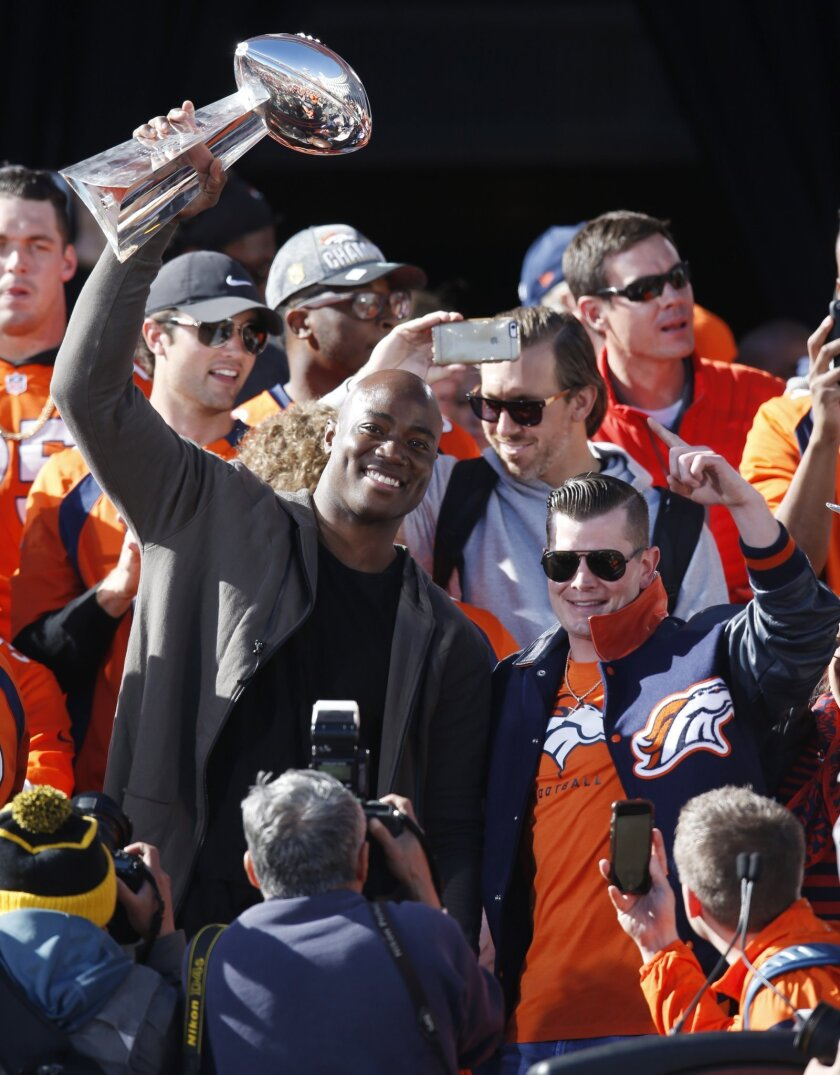 Denver Broncos outside linebacker DeMarcus Ware, left, hoists the Lombardi Trophy as John Bowlen, son of team owner Pat Bowlen, looks on at a rally following a parade through downtown Tuesday, Feb. 9, 2016 in Denver. Fans crowded into Denver's downtown to salute the Broncos for the team's victory o