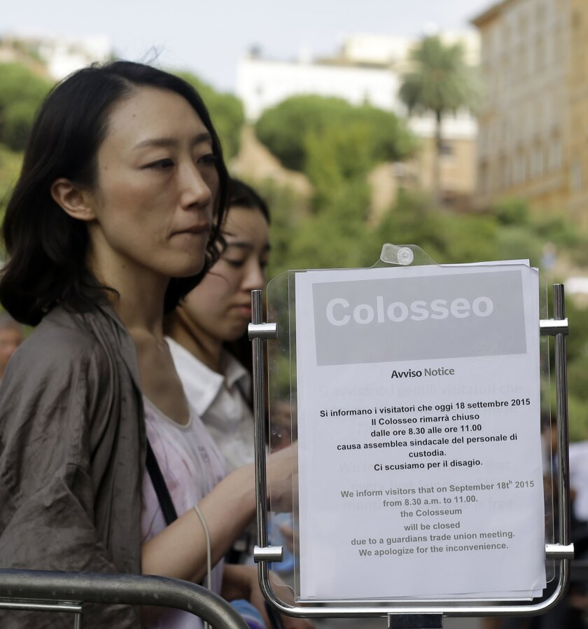 Tourists, queuing to enter the Colosseum, walk past a notice informing visitors of the monument's temporary closure Friday morning due to an archaeological workers union meeting, in Rome, Friday, Sept. 18, 2015. (AP Photo/Gregorio Borgia)
