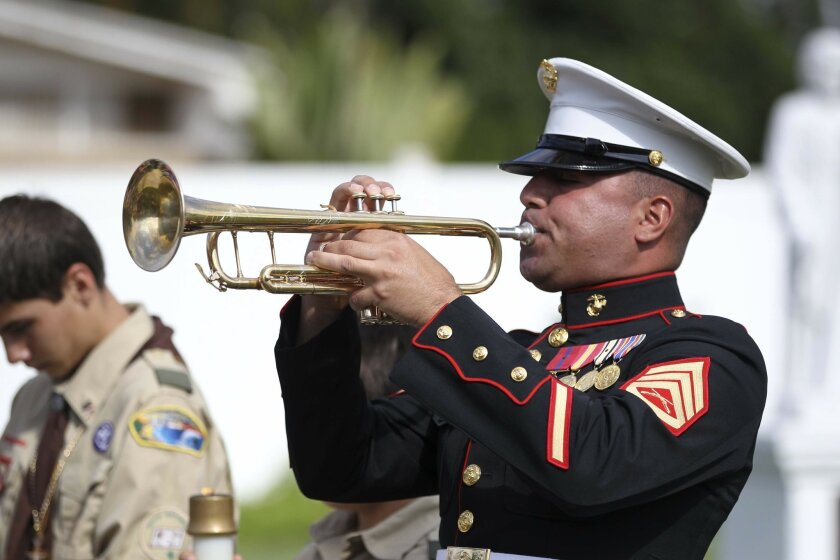 Dozens of people shared a prayer and listened as Marine Corps Staff Sgt. Steven Santiago, shown here,  played taps at the San Luis Rey Mission cemetery in Oceanside on Monday, May 27, 2013 during a morning Memorial Day remembrance ceremony.