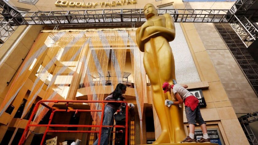 Workers touch up a giant Oscar statue on the red carpet entrance at the Dolby Theatre in Hollywood on Feb. 23, 2016.