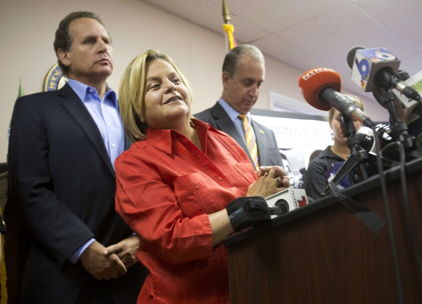 U.S. Rep. Ileana Ros-Lehtinen, R-Fla., center, listens to a question from the media on Aug. 12, 2015. She announced Sunday that she will not seek re-election in 2018.
