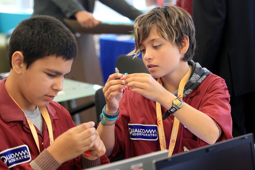 Carl Proctor, 13, left, and Bleu Pietrafeso, both 13 and both students at Roosevelt Middle School, work on a project involving LED lights at Qualcomm's Linkabit laboratory.
