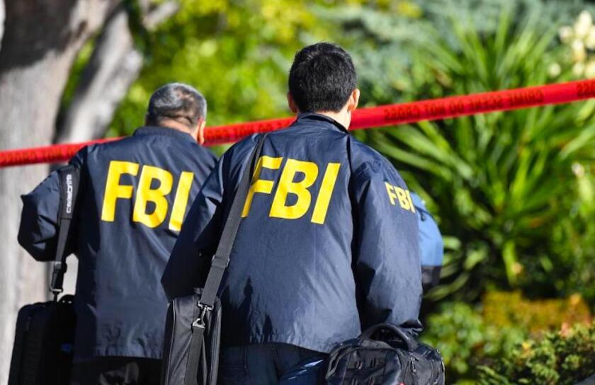 """Two men wear """"FBI""""-branded windbreakers."""