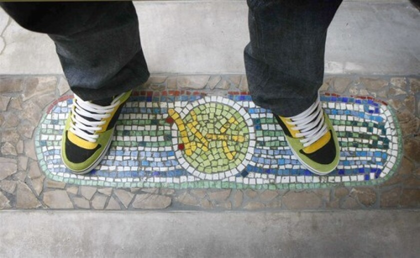 Pierre Andre Senizergues takes a familiar stance on a patio mosaic.