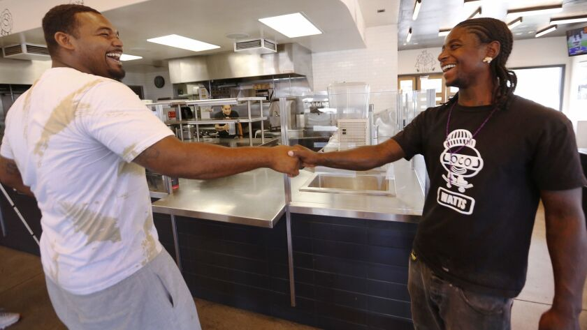 LOS ANGELES, CA – AUGUST 21, 2018: Locol restaurant in Watts customer Miles Glasgow, left, greets