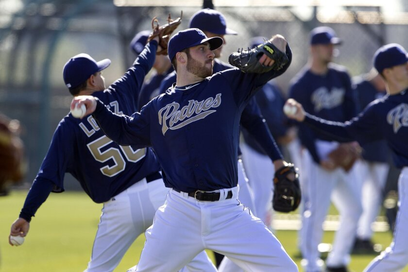 Pitcher Anthony Bass, front, tosses the ball during the first workout day of Padres spring training Wednesday in Peoria, Arizona.
