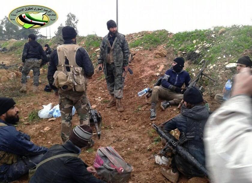 """ARCHIVO - En esta foto de archivo del 14 de diciembre de 2014, combatientes del Frente Nusra vinculado con Al Qaeda y de otras facciones rebeldes descansan después de enfrentamientos con las fuerzas sirias en Wadi Deif, en la provincia de Idlib, en el noroeste de Siria. La imagen fue facilitada por el grupo activista antigubernamental Observatorio Sirio para los Derechos Humanos y fue autentificada con base a su contenido y despachos de The Associated Press. La organización Amnistía Internacional, con sede en Londres, dijo en un informe difundido el martes 5 de julio que algunos grupos de la oposición armada en Siria cometen abusos similares a las del gobierno del presidente Bashar Assad después de que documentara una """"escalofriante"""" ola de torturas, secuestros y ejecuciones sumarias en zonas controladas por la insurgencia. (AP Foto/Observatorio Sirio para los Derechos Humanos, Archivo)"""