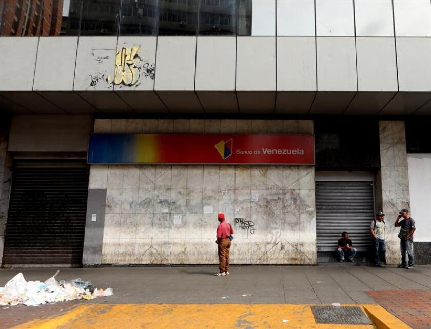 Venezuelans wait in front of a bank without service during the power outage in Caracas, Venezuela. on March 8, 2019. EPA-EFE/RAYNER PEÑA