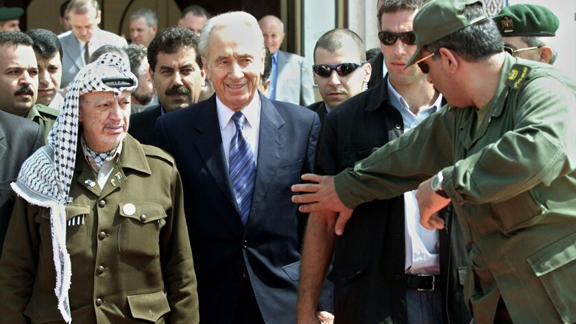 Israeli Foreign Minister Shimon Peres, center, and Palestinian leader Yasser Arafat, left, leave a meeting in the Gaza Strip on Sept. 26, 2001.