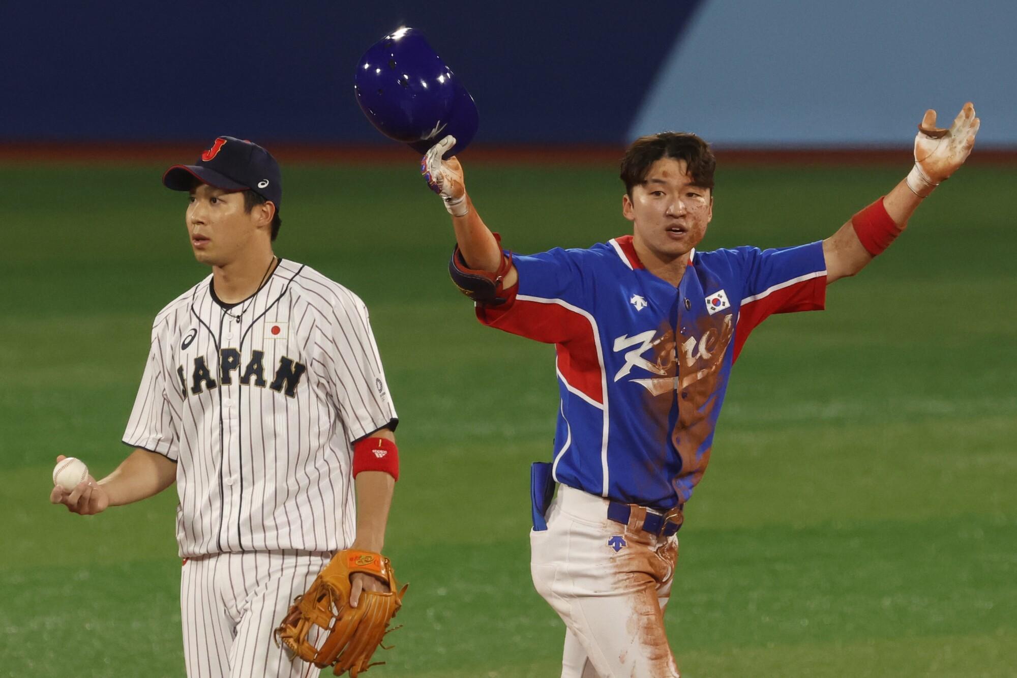 South Korea outfielder Hae Min Park celebrates next to Japan infielder Tetsuto Yamada.
