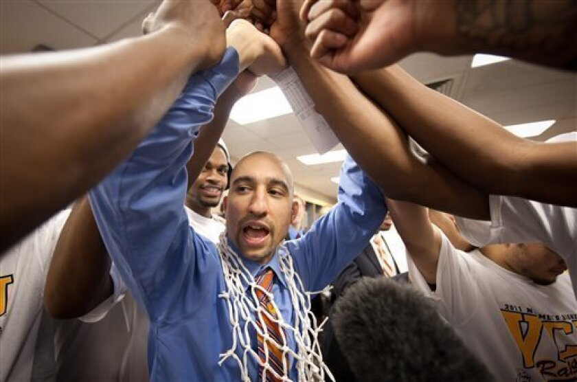 In this photo provided by Virginia Commonwealth, VCU head coach Shaka Smart celebrates with his team after winning the Southwest regional final game against Kansas in the NCAA college basketball tournament Sunday, March 27, 2011, in San Antonio. VCU won 71-61. (AP Photo/Virginia Commonwealth, Scott K. Brown) NO SALES