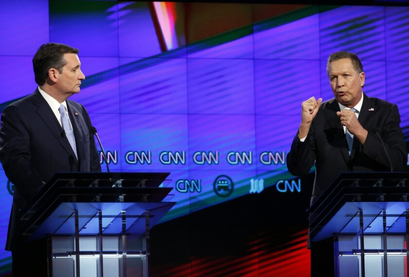 FILE - In this March 10, 2016, file photo, Republican presidential candidate Ohio Gov. John Kasich, right, speaks as Republican presidential candidate, Sen. Ted Cruz, R-Texas, listens, during a Republican presidential debate sponsored by CNN, Salem Media Group and the Washington Times at the Univer