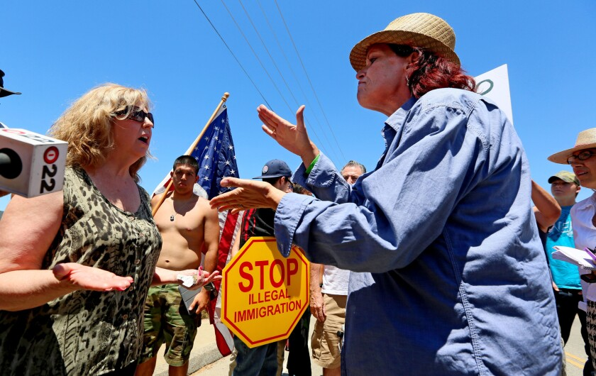 Anti-immigration activist Sabina Durden, right, and immigration supporter Mary Estrada, left, debate during a protest outside of the U.S. Border Patrol Murrieta Station on Monday.